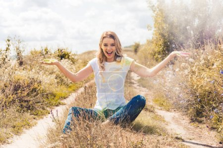 Photo for Attractive and blonde woman smiling and throwing colorful powder - Royalty Free Image