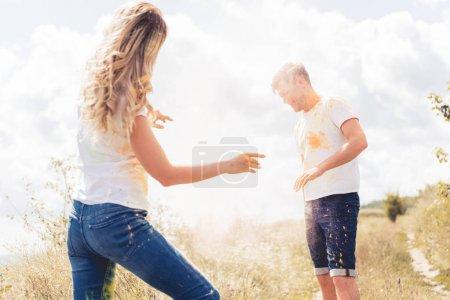 Photo pour Femme et bel homme dans des t-shirts jetant la poudre colorée - image libre de droit