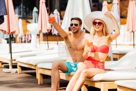 Photo for Happy smiling couple holding cocktails at resort in sunny day - Royalty Free Image