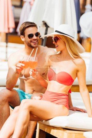 Photo pour Verres heureux de couples de sourire clignotant avec des cocktails et regardant l'un l'autre à la ressource dans la journée ensoleillée - image libre de droit