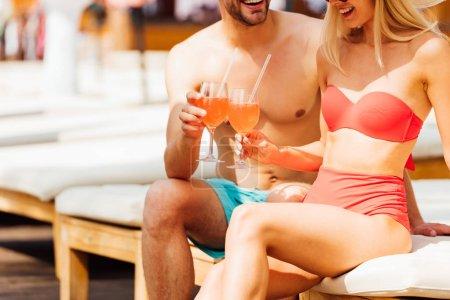 Photo pour Vue partielle de couples heureux de sourire retenant des cocktails à la ressource dans la journée ensoleillée - image libre de droit