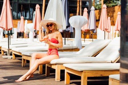 Photo pour Fille sexy en maillot de bain tenant cocktail et souriant à la station dans la journée ensoleillée - image libre de droit