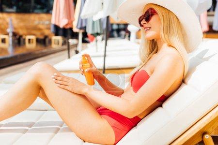 Photo pour Sexy jeune femme sur chaise longue appliquant écran solaire dans la journée ensoleillée - image libre de droit