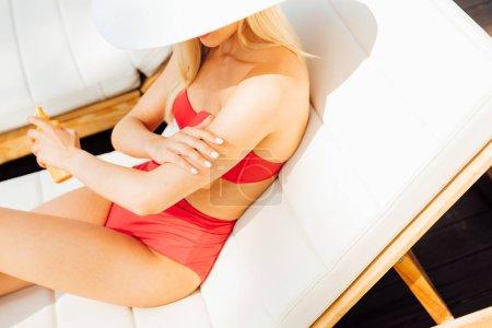Photo pour Jeune femme sexy sur le transat appliquant la protection solaire dans la journée ensoleillée - image libre de droit
