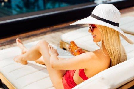 Photo pour Souriant sexy jeune femme sur chaise longue appliquant crème solaire dans la journée ensoleillée - image libre de droit