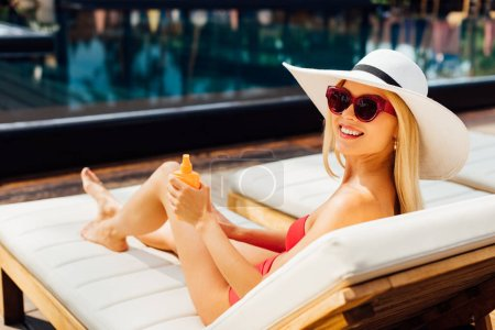 Photo for Smiling sexy young woman on lounger applying sunscreen in sunny day - Royalty Free Image