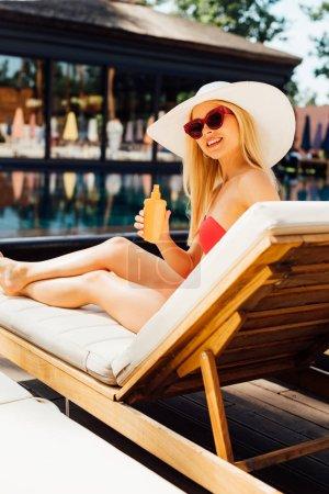 Photo pour Jeune femme sexy de sourire sur la protection de chaise longue retenant la protection solaire dans le jour ensoleillé - image libre de droit
