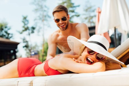 Photo for Smiling man in sunglasses doing massage for girlfriend at resort - Royalty Free Image