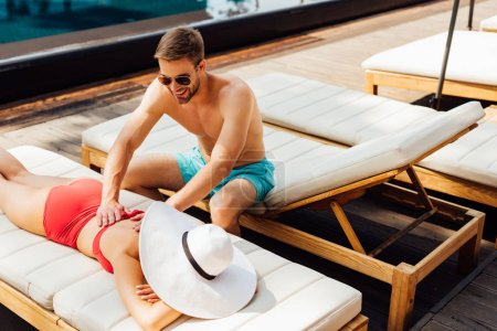 smiling man in sunglasses doing massage for girlfriend at resort