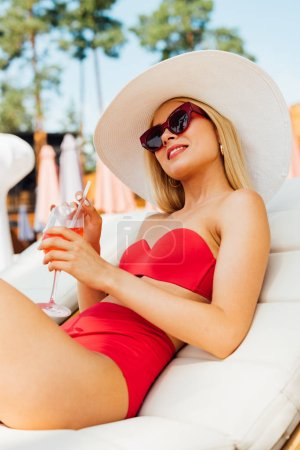 Photo pour Sexy girl in sunglasses lying on lounger with cocktail - image libre de droit