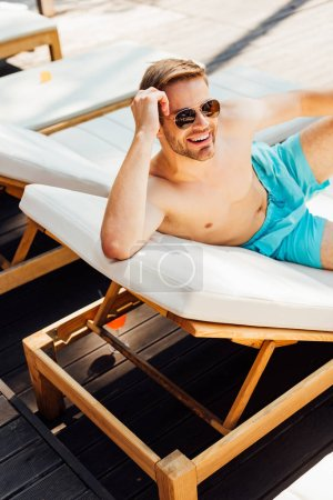 happy shirtless man in sunglasses lying on lounger at resort
