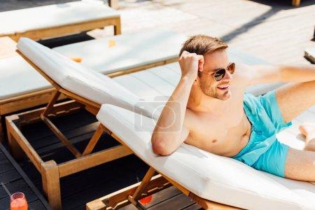 Photo pour Homme torse nu heureux dans des lunettes de soleil couché sur une chaise longue à la station - image libre de droit