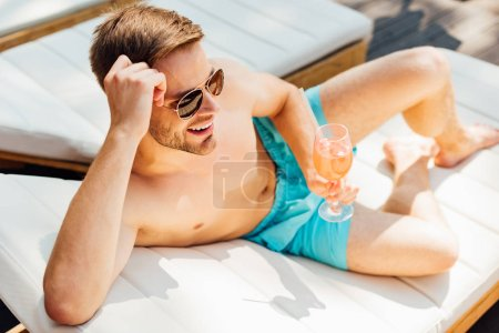Photo for Happy shirtless man in sunglasses lying on lounger and holding glass of cocktail at resort - Royalty Free Image