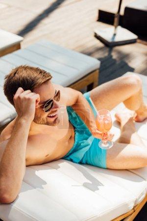 Photo pour Homme torse nu heureux dans des lunettes de soleil couché sur une chaise longue et tenant un verre de cocktail à la station - image libre de droit