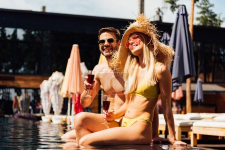 Photo for Sexy couple holding glasses of red wine and smiling in swimming pool - Royalty Free Image