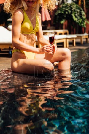 partial view of sexy girl holding glass of red wine at resort