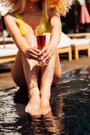 Photo pour Vue partielle de fille sexy tenant verre de vin rouge à la station - image libre de droit