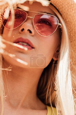 Photo for Pensive attractive girl in sunglasses and straw hat looking up - Royalty Free Image