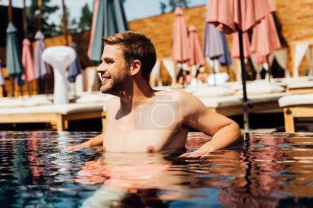 feliz hombre joven sin camisa en la piscina en el día soleado