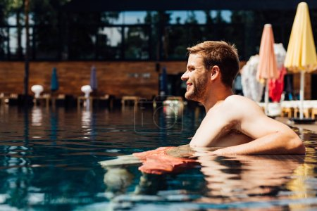Photo for Happy shirtless young man in swimming pool in sunny day - Royalty Free Image