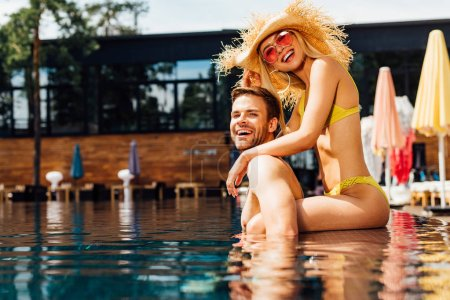 Photo for Sexy happy couple embracing in swimming pool in sunny day - Royalty Free Image