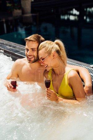Photo pour Couples sexy retenant des glaces de vin rouge embrassant dans la piscine dans le jour ensoleillé - image libre de droit