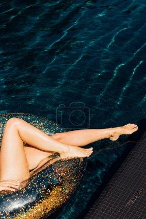 Photo pour Vue partielle de jeune femme sexy se trouvant sur l'anneau de natation dans la piscine dans le jour ensoleillé - image libre de droit