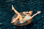 """Постер, картина, фотообои """"сексуальная девушка в купальнике и солнцезащитных очках улыбается на плавать кольцо в бассейне"""""""