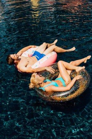 Photo pour Couples nu-pieds heureux se trouvant sur des anneaux de natation dans la piscine - image libre de droit