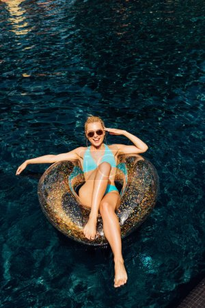 Foto de Chica sexy descalzo en traje de baño acostado en el anillo de natación en la piscina - Imagen libre de derechos