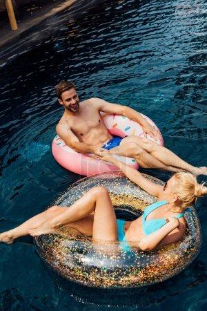 Photo pour Couple souriant tenant la main et se regardant tout en étant couché sur des anneaux de natation dans la piscine - image libre de droit