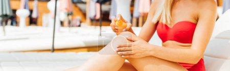 Photo pour Tir panoramique de fille sexy dans le maillot de bain appliquant la protection solaire à la station - image libre de droit