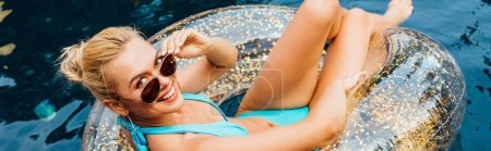 Photo for Panoramic shot of smiling sexy young woman in swimsuit and sunglasses lying on swim ring in pool - Royalty Free Image
