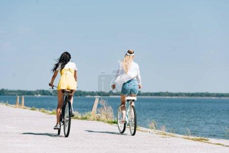 Photo pour Vue arrière des filles blondes et brunes conduisant des vélos près de la rivière en été - image libre de droit