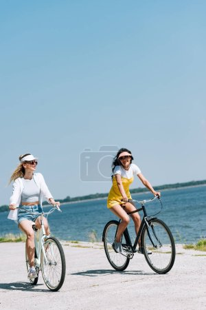 Photo for Blonde and brunette girls riding bikes near river in summer - Royalty Free Image