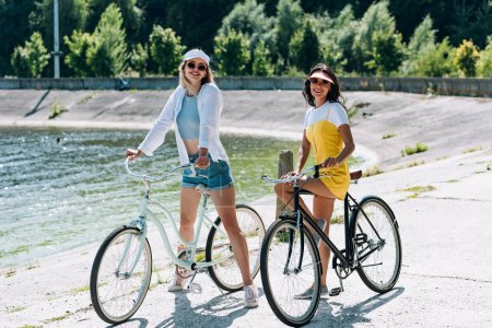 Photo for Happy blonde and brunette girls riding bikes near river in summer - Royalty Free Image
