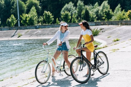 Photo for Happy blonde and brunette girls with bikes looking at each other near river in summer - Royalty Free Image