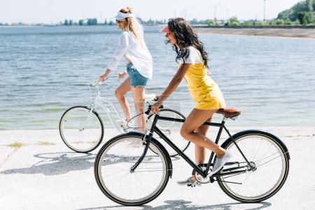 Photo pour Vue de côté des filles blondes et brunes de sourire conduisant des vélos près de la rivière en été - image libre de droit