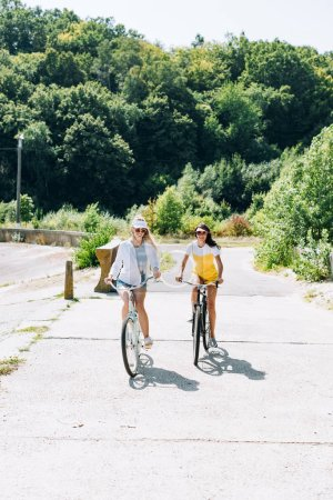 Photo for Happy blonde and brunette girls riding bikes in summer - Royalty Free Image