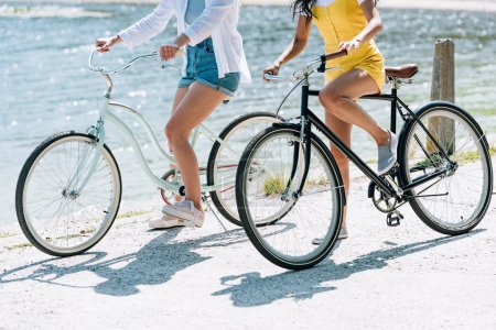 Photo for Cropped view of girls riding bikes near river in summer - Royalty Free Image