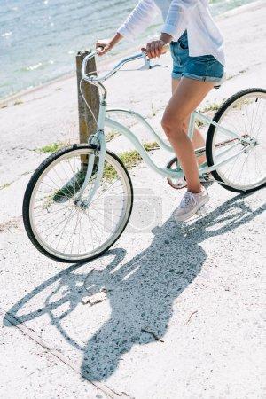 Photo pour Vue recadrée de vélo d'équitation de fille près de la rivière en été - image libre de droit