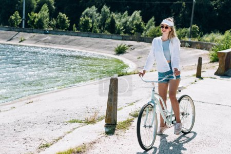 Photo for Blonde beautiful girl riding bicycle near river in summer - Royalty Free Image