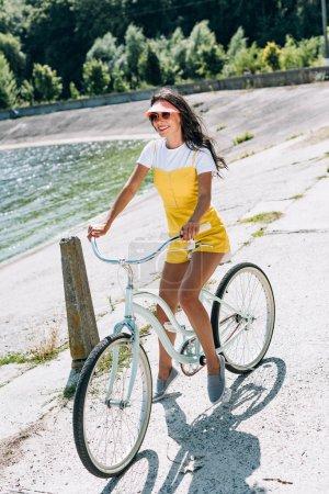 Photo pour Brunette belle fille équitation vélo près de la rivière en été - image libre de droit