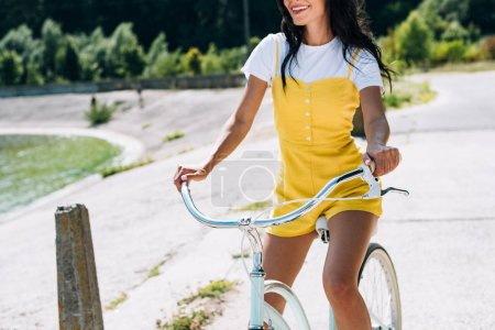 Photo for Cropped view of brunette beautiful girl riding bicycle near river in summer - Royalty Free Image
