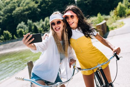 Photo for Selective focus of blonde and brunette girls showing tongues while taking selfie on bikes - Royalty Free Image