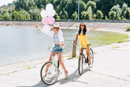 Photo for Happy blonde and brunette girls riding bikes with balloons near river in summer - Royalty Free Image