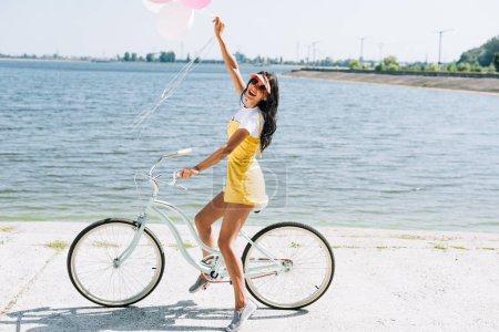 Foto de Vista lateral de la chica morena feliz montando en bicicleta con globos cerca del río en verano - Imagen libre de derechos