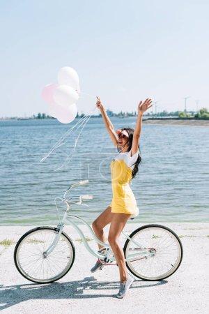 Photo pour Vue de côté de vélo d'équitation heureux de fille de brunette avec des ballons et des mains dans l'air près de la rivière en été - image libre de droit