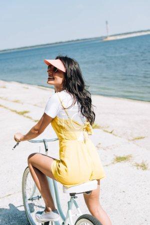 Foto de Morena feliz chica montando en bicicleta cerca del río en verano - Imagen libre de derechos