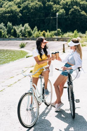 Photo for Happy blonde and brunette girls with bikes and coffee to go near river in summer - Royalty Free Image
